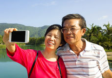 Senior couple taking picture by themselves in outside Royalty Free Stock Photo