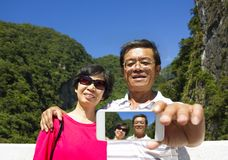 Senior couple taking picture of themselves outside Royalty Free Stock Photo