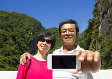 Senior couple taking picture of themselves outside Stock Image