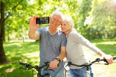 Senior couple taking selfie. Senior couple with bicycles taking selfie Stock Photography