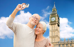 Senior couple taking selfie on camera over big ben Stock Images