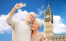 Senior couple taking selfie on camera over big ben Stock Images