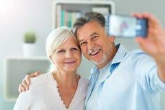 Senior couple taking selfie. At home Stock Photo