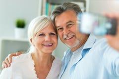 Senior couple taking selfie. Senior couple at home, smiling Royalty Free Stock Image