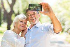 Senior couple taking selfie. Loving senior couple standing outdoors Royalty Free Stock Photography