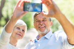 Senior couple taking selfie. Loving senior couple standing outdoors Stock Images