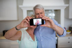 Senior couple taking selfie on mobile phone Royalty Free Stock Image