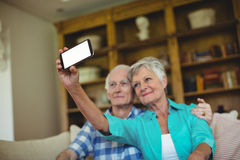 Senior couple taking a selfie on mobile phone in living room Royalty Free Stock Photography