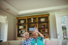 Senior couple taking a selfie on mobile phone in living room Royalty Free Stock Image