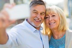 Senior couple taking selfie. Outdoors Stock Photo
