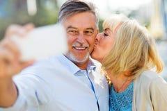 Senior couple taking selfie. Outdoors Royalty Free Stock Image