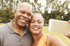 Senior Couple Taking Selfie In Park Stock Photos