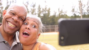 Senior Couple Taking Selfie In Park