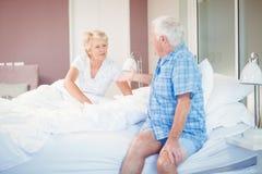 Senior couple talking in bedroom Stock Photos
