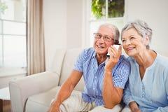Senior couple talking on mobile phone Royalty Free Stock Photos