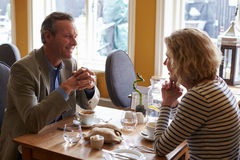 Senior couple talking at a restaurant, side view Stock Image