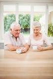 Senior couple talking to each other while having coffee Royalty Free Stock Photos