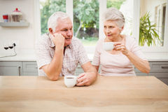 Senior couple talking to each other while having coffee Royalty Free Stock Images