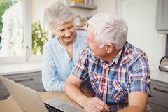 Senior couple talking while using laptop Stock Images