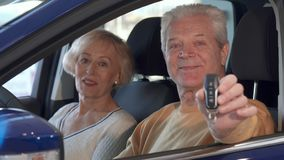 Senior couple talks inside the car. Attractive senior couple talking inside the car at the dealership. Aged caucasian men and women sitting on the front seats of Royalty Free Stock Images