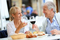 Senior couple tasing local food and drinking wine Stock Images