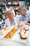 Senior couple tasting local food in outdoor restaurant Stock Photo