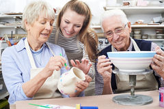 Senior Couple With Teacher In Pottery Class. Senior Couple And Teacher In Pottery Class royalty free stock image