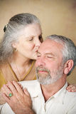 Senior Couple - Tender Kiss. Beautiful senior women gives her husband a loving kiss on the forehead.  Vignette added for dramatic effect Stock Images