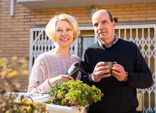 Senior couple on a terrace. Near their home. Mature women is holding gardening accesories and men is drinking tea from a cup stock photography