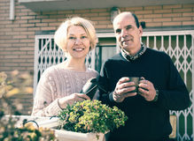 Senior couple on a terrace. Near their home. Mature women is holding gardening accesories and men is drinking tea from a cup royalty free stock images