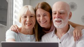 Senior couple and their daughter sitting at home talking via messenger Skype. Smiling laughing. Senior couple and their young daughter sitting at home talking stock video