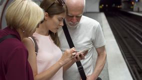 Senior couple and their daughter traveling by subway. Standing waiting for train, browsing in mobile. Senior couple and their young daughter traveling by subway stock footage