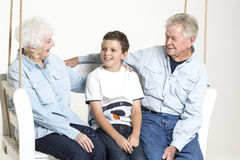 Senior couple with their grandson. Senior couple is having conversation on a swing with their grandson Stock Photos