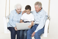 Senior couple with their grandson. Senior couple is having conversation on a swing with their grandson who helps them with computer problem Royalty Free Stock Photography