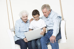 Senior couple with their grandson. Senior couple is having conversation on a swing with their grandson who helps them with computer problem Stock Image