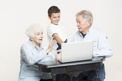 Senior couple with their grandson. Senior couple is having conversation on a swing with their grandson who helps them with computer problem Stock Images