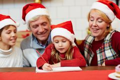 Girl drawing. Senior couple and their grandson looking at little girl with crayon drawing xmas picture in notepad Royalty Free Stock Photography
