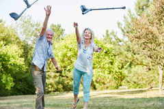 Senior couple throws crutches in the air. Senior couple in the park playfully throws crutches in the air Royalty Free Stock Images