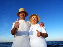 Senior couple thumbs up laughing on beach Royalty Free Stock Photo
