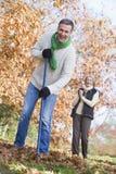 Senior couple tidying autumn leaves