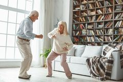 Senior couple together at home retirement concept dancing active dance playful. Aged men and women together at home in the living room dancing active dance royalty free stock photo