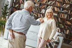 Senior couple together at home retirement concept dancing ballroom dance invitation. Aged men and women together at home in the living room dancing invitation royalty free stock images
