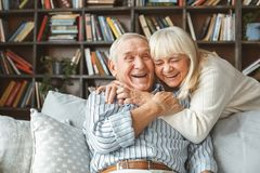 Senior couple together at home retirement concept hugging laughing. Aged man sitting and woman standing together at home in the living room hugging laughing royalty free stock photo