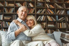 Senior couple together at home retirement concept hugging looking camera. Aged men and women together at home in the living room sitting on the coach hugging stock photography