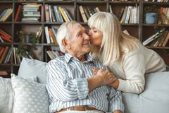 Senior couple together at home retirement concept kiss. Aged men sitting and women standing together at home in the living room kissing holding hands smiling royalty free stock photography