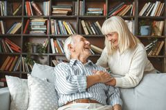 Senior couple together at home retirement concept looking on each other holding hands. Aged men sitting and women standing together at home in the living room stock image