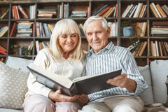 Senior couple together at home retirement concept photograph album front view. Aged men and women together at home in the living room looking through photograph stock photography