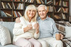 Senior couple together at home retirement concept sitting drinking tea. Aged men and women together at home in the living room sitting drinking hot tea smiling royalty free stock images