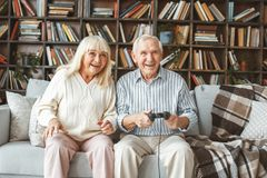 Senior couple together at home retirement concept sitting playing excited. Aged men and women together at home in the living room sitting playing game excited royalty free stock photography