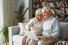 Senior couple together at home retirement concept sitting using laptop pointing at the screen. Aged men and women together at home in the living room sitting royalty free stock photo